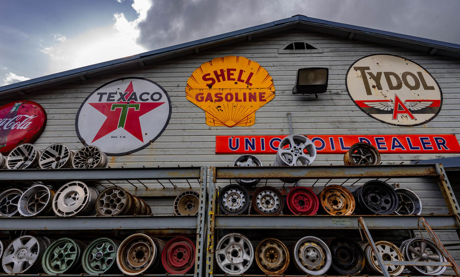 Junk Yard Old Cars Architecture Building Exterior Built Structure Car Wheels Circle Cloud - Sky Communication Day Heart Shape Information Information Sign Low Angle View No People Outdoors Script Shape Sign Sky Text Western Script