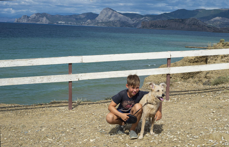 Boy with a dog on the background of the seascape. friendship of children with pets. traveling.
