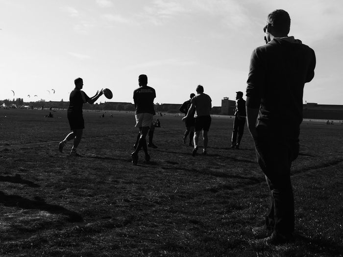 Men Playing Rugby On Field Against Sky