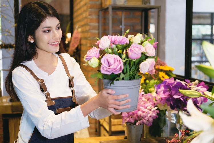 Smiling Young Woman Holding Bouquet In Store