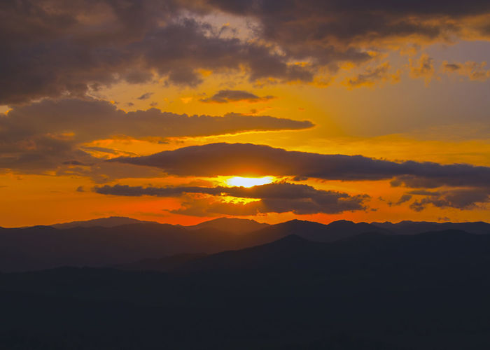 Silhouette Of Mountain Against Cloudy Sky During Sunset