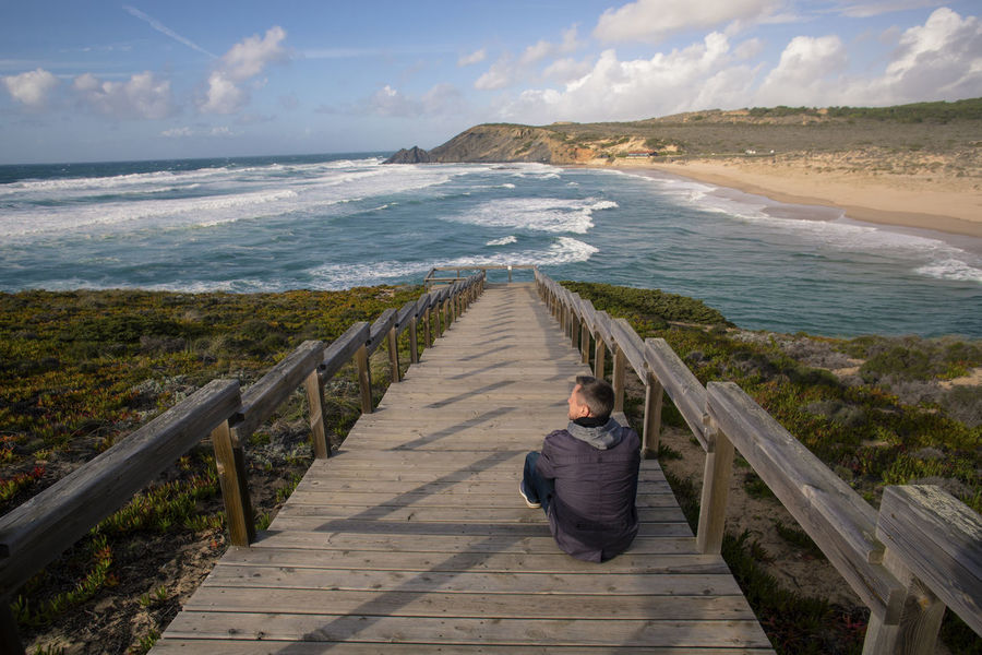 Man sitting on boardwalk and looking at the Atlantic ocean. 45-50 Atlantic Ocean Perspectives on Nature Sitting Beach Beauty In Nature Boardwalk Caucasian Footbridge Horizon Over Water Leisure Activity Lifestyles One Person Outdoors Railing Real People Scenics - Nature Sea Sky Sunset The Way Forward Tranquil Scene Tranquility Water Wood - Material