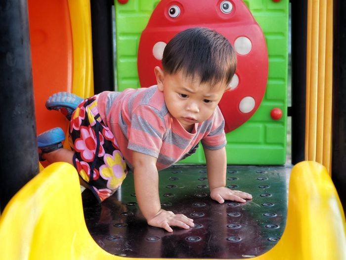 Cute boy playing on slide at playground
