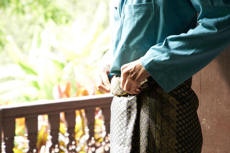 Midsection of man adjusting samping during ramadan festival