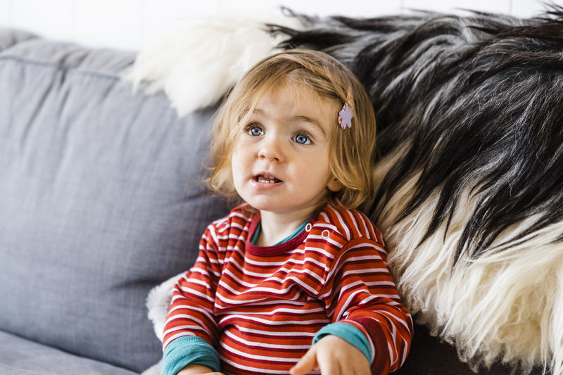 Cute Girl Looking Away While Sitting On Sofa At Home