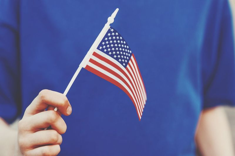 a young man holding a flag in honor of America's Independence Day Human Hand Patriotism Flag Hand One Person Human Body Part Holding Striped Human Finger Pride Freedom Body Part Finger Independence Real People National Icon Blue Unrecognizable Person