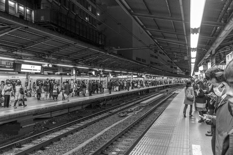 People waiting at railroad station platform at night