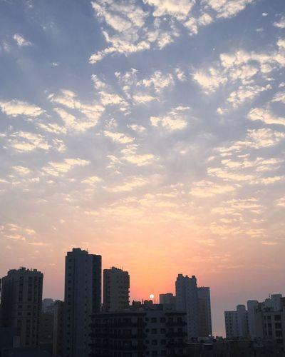 Modern cityscape against sky during sunset