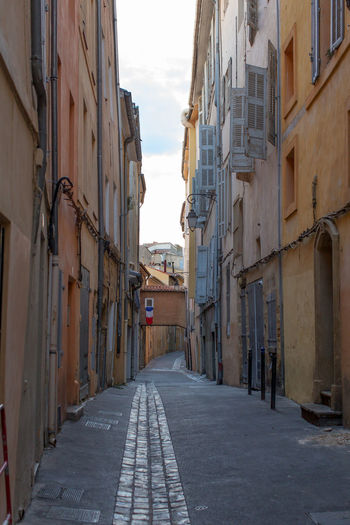 A narrow street at the Old city of Aix-en-Provence 0ld City Alley Architecture Building Exterior Built Structure City City Life Day Diminishing Perspective Long Narrow National Flag Outdoors Sky Street Tall The Way Forward
