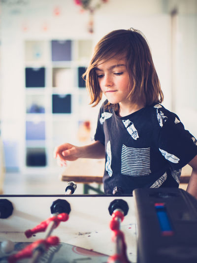 Boy Kickertisch Fussball Football Real People Childhood One Person Child Indoors  Standing Lifestyles Girls Women Leisure Activity Waist Up Females Holding Front View Hairstyle Focus On Foreground Long Hair Toy Innocence