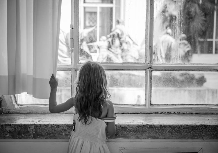 Rear view of girl looking through window at home