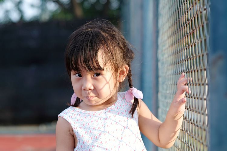 Portrait of cute girl touching chainlink fence