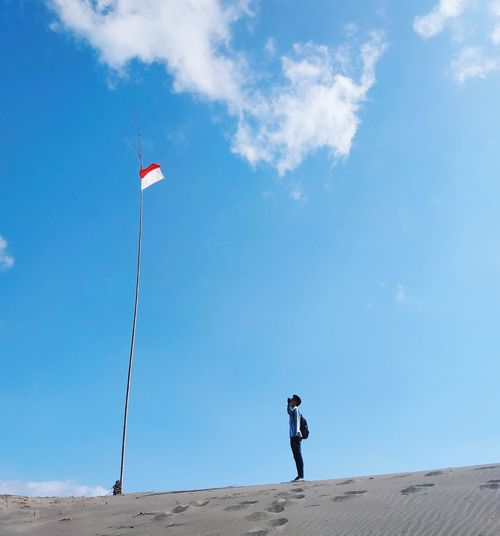 Man standing at beach against blue sky