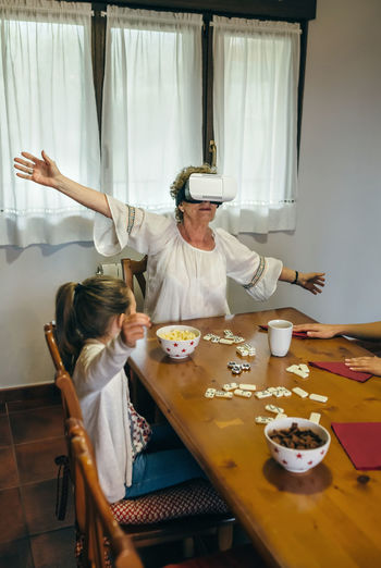 Senior woman wearing virtual reality headshot while sitting with granddaughter at table