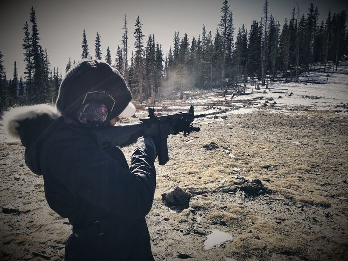 Woman Aiming Rifle While Standing In Forest During Winter