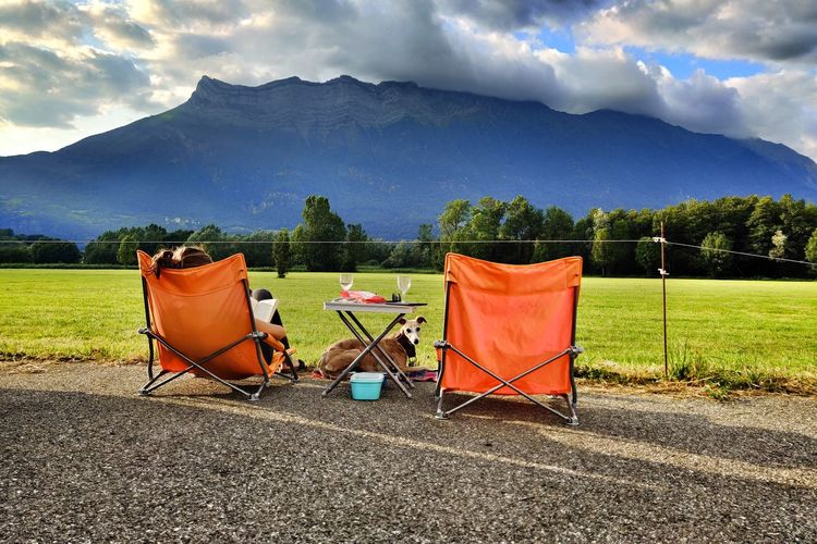 Deck chairs on field against sky