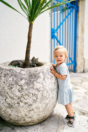 Cute boy standing on potted plant