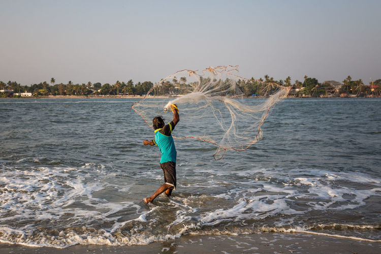 Fisherman at the Beach of Kochi, India Cochin Fish Fisher Fisherman Fishermen Fishing Fishing Net Food India Indian Kerala Kochi Ocean One Animal One Person One Person Only Outdoors People Seafood Sunet Throw Tourism Waves