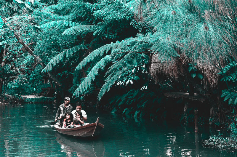 People in boat against trees