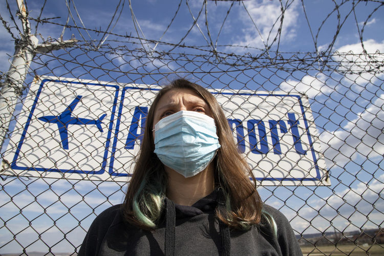 Low angle view of woman wearing mask standing against fence