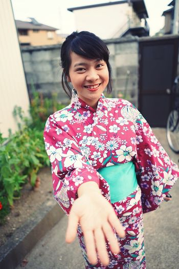 Portrait of smiling young woman wearing kimono gesturing outdoors