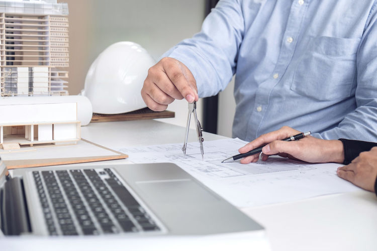 Midsection of business people working at desk in office
