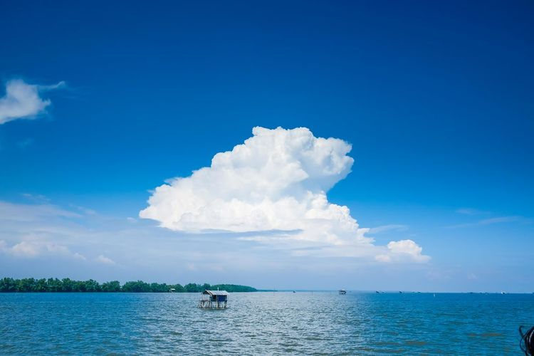 Scenic view of built structures in sea against blue sky