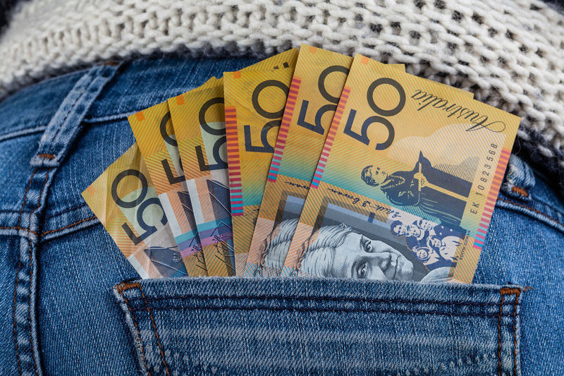 Midsection of woman putting australian currency in pocket