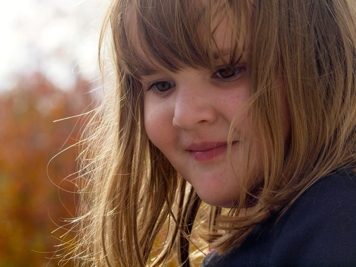 Close-up of smiling girl looking away