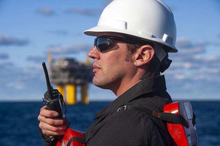 Portrait of man holding sunglasses in sea
