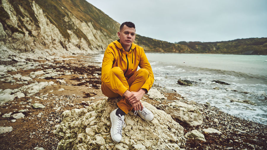 Full length portrait of young man sitting on rock at beach