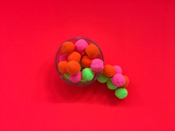 Close-Up Of Colorful Candies In Bowl Over Red Background