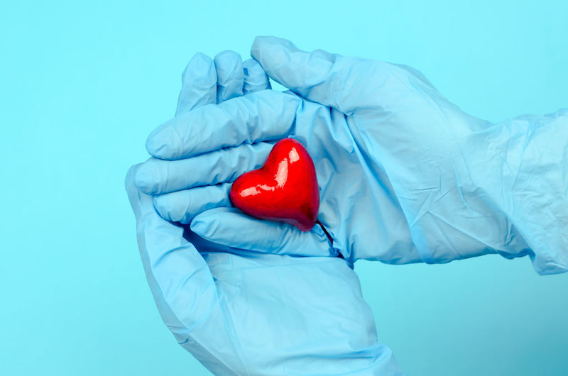 Close-up of man holding heart shape against blue background