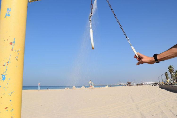 Man taking a shower on beach against clear blue sky