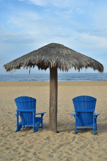 Blue beach chairs under thatched umbrella on beach sand baja mexico