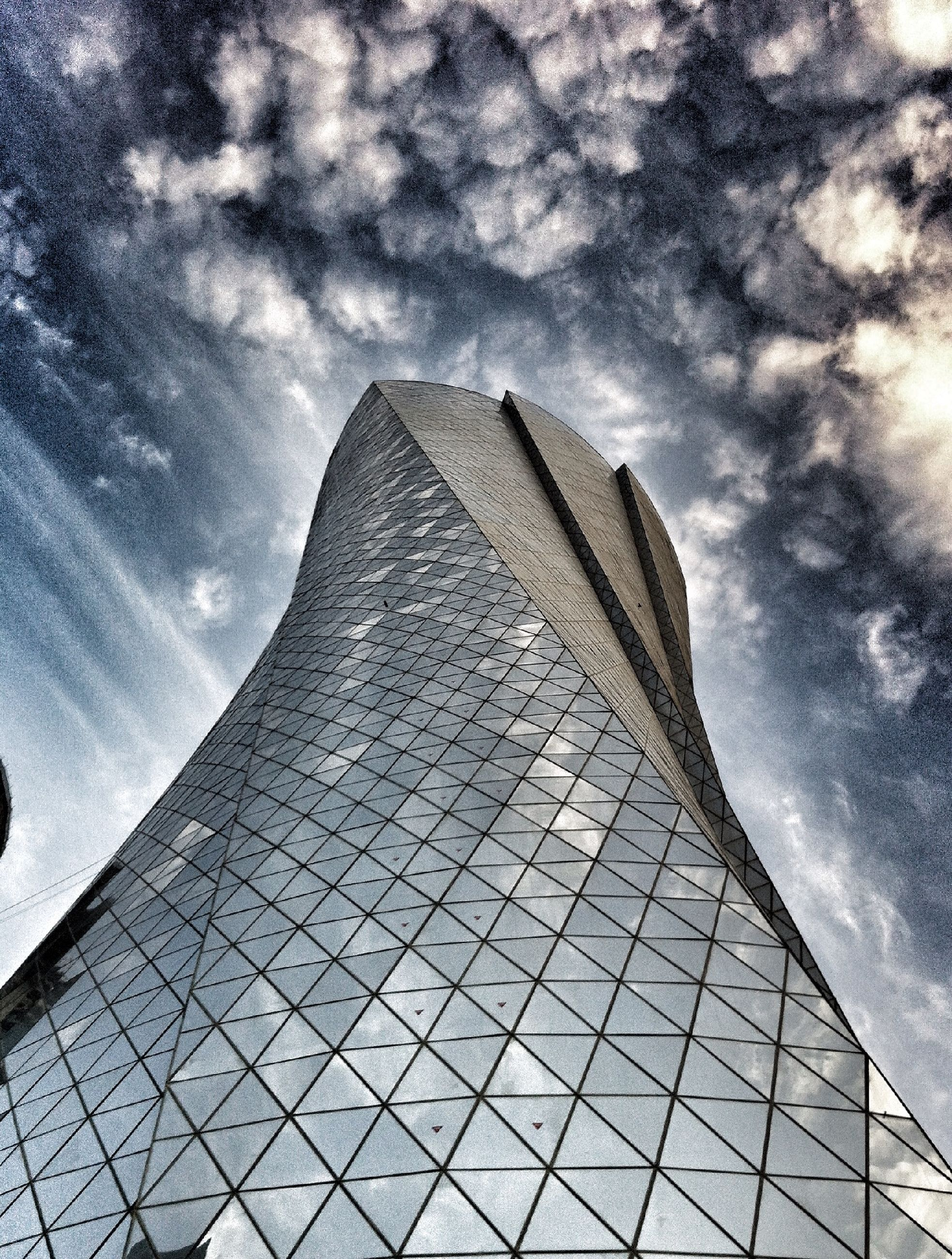 architecture, built structure, low angle view, building exterior, sky, cloud - sky, modern, cloudy, tower, tall - high, cloud, office building, glass - material, city, building, architectural feature, skyscraper, day, reflection, outdoors