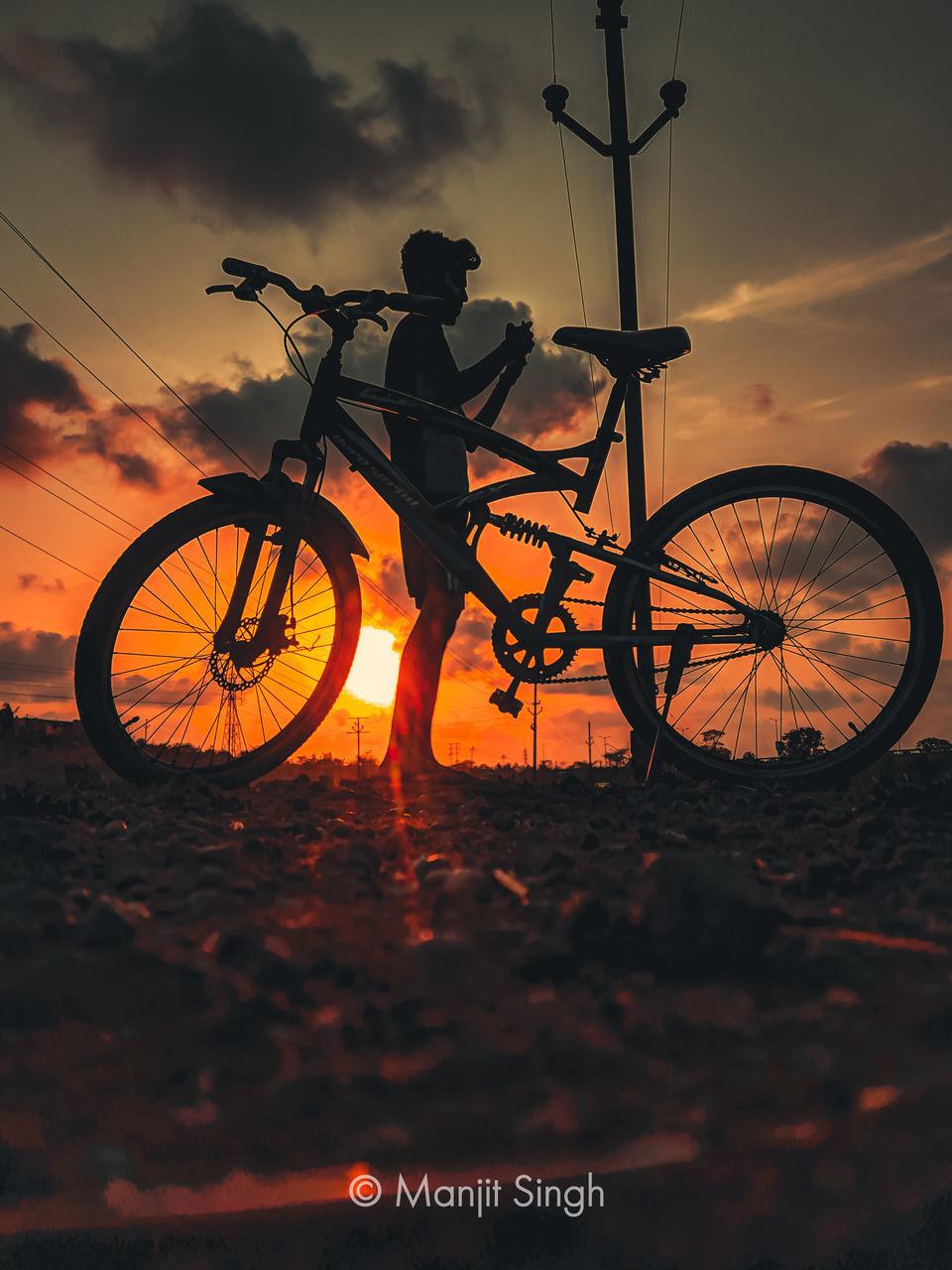 SILHOUETTE BICYCLE AGAINST ORANGE SKY