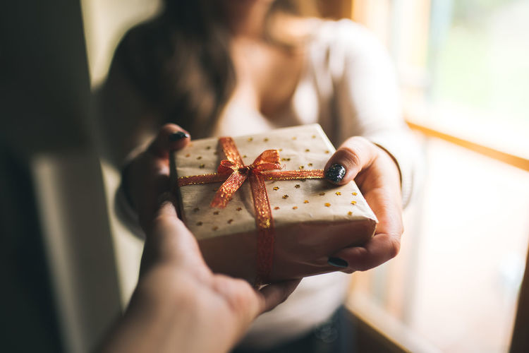 Midsection of woman giving gift box to friend against window