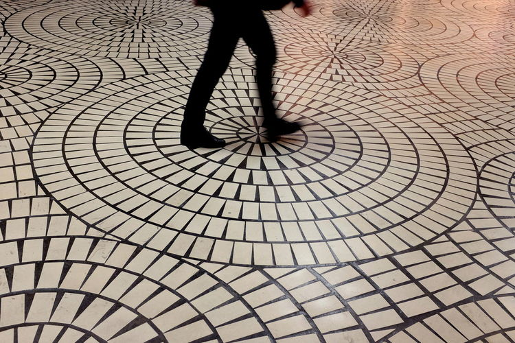 Low section of man walking on tiled floor