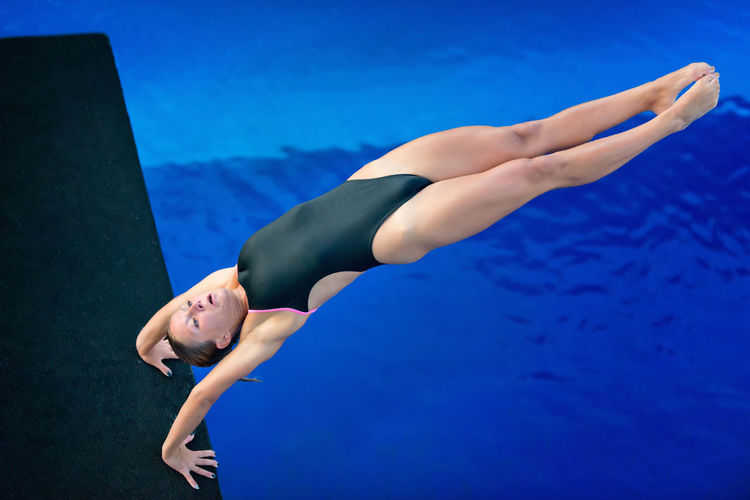 Armstand Back Dive, Moment Of Take-Off Swimming Diving Armstand Armstand Dive Athlete Diving Board Horizontal Individual Sports Water Sport Woman Blue Dive Female Muscular Build One Person Outdoors Pool Sport Strength Swimming Pool Water Young Adult Young Women