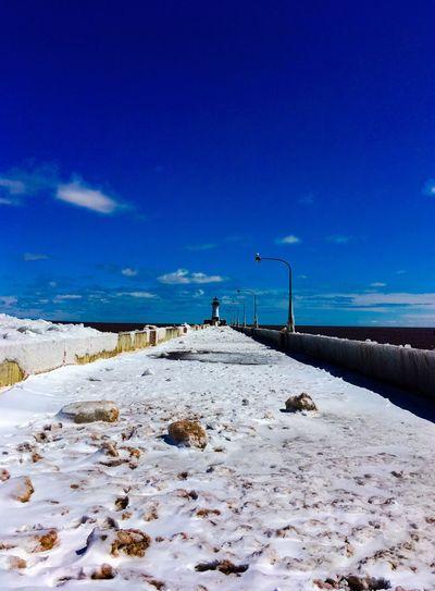Snow covered pier against blue sky