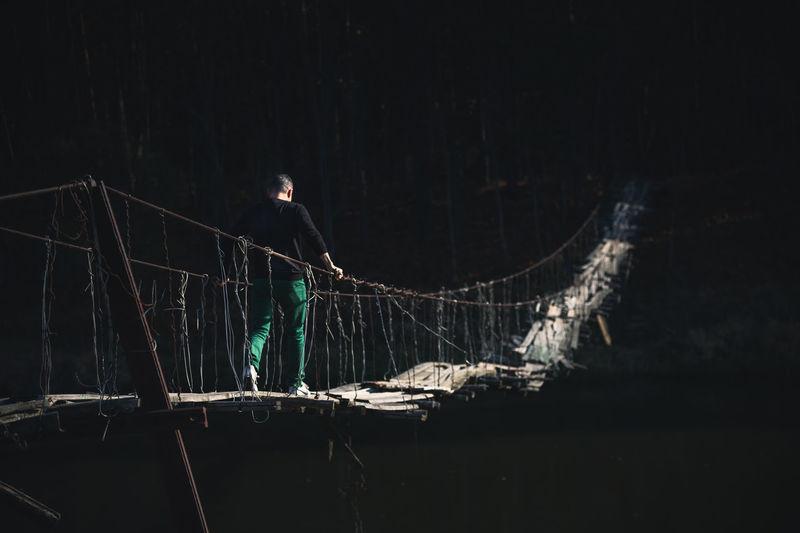 Man standing on illuminated land at night