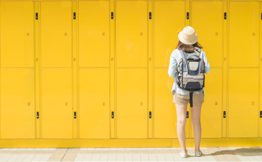 Rear View Full Length Of Woman Standing Against Yellow Lockers