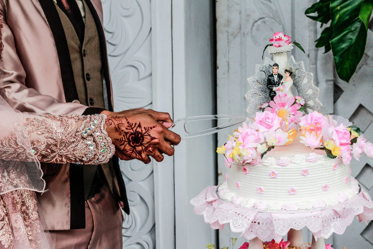 Midsection of bride and bridegroom cutting wedding cake