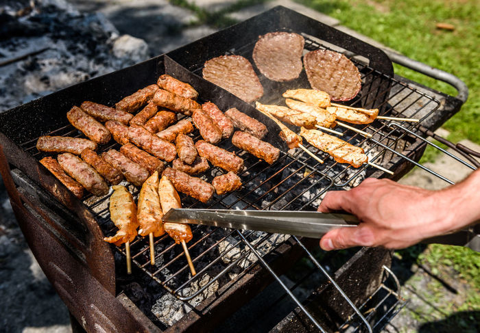 Delicious meat on barbecue grill with coal outdoors picnic. Grilling food on backyard or a terrace Old small cheap BBQ grill at home. BBQ Grid Grilling Hot Skewers Barbecue Barbecue Grill Bbq Grill Burgers Cevapcici Cevapi Coal Day Delicious Food Fresh Grill Making Meat No People Outdoors Preparing Preparing Food