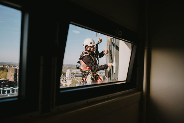 Abseilers cleaning windows on a tall building Carabina Window Cleaner Working Abseiling Day Indoors  Manual Worker Men Occupation Real People Ropes Skill  Window Window Cleaning Window Washer Windows Working