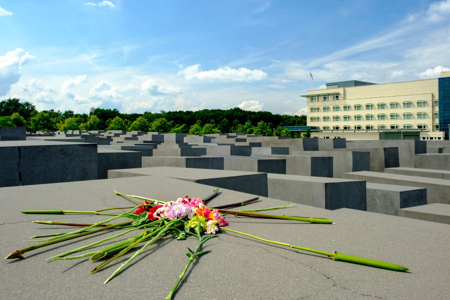 A bouquet of flowers left behind on one of the concrete stelae at the Memorial to the Murdered Jews of Europe (Denkmal für die emordeten Juden Europas), constructed in 2003-2004. The U.S. Embassy is in the background. Memorial World War 2 Architecture Bouquet Building Exterior Built Structure Clouds Flower Holocaust Memorial Jewish Memorial Monument No People Outdoors Rememberance Sky War