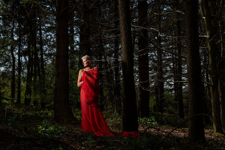 Senior Woman With Red Scarf Standing By Trees In Forest
