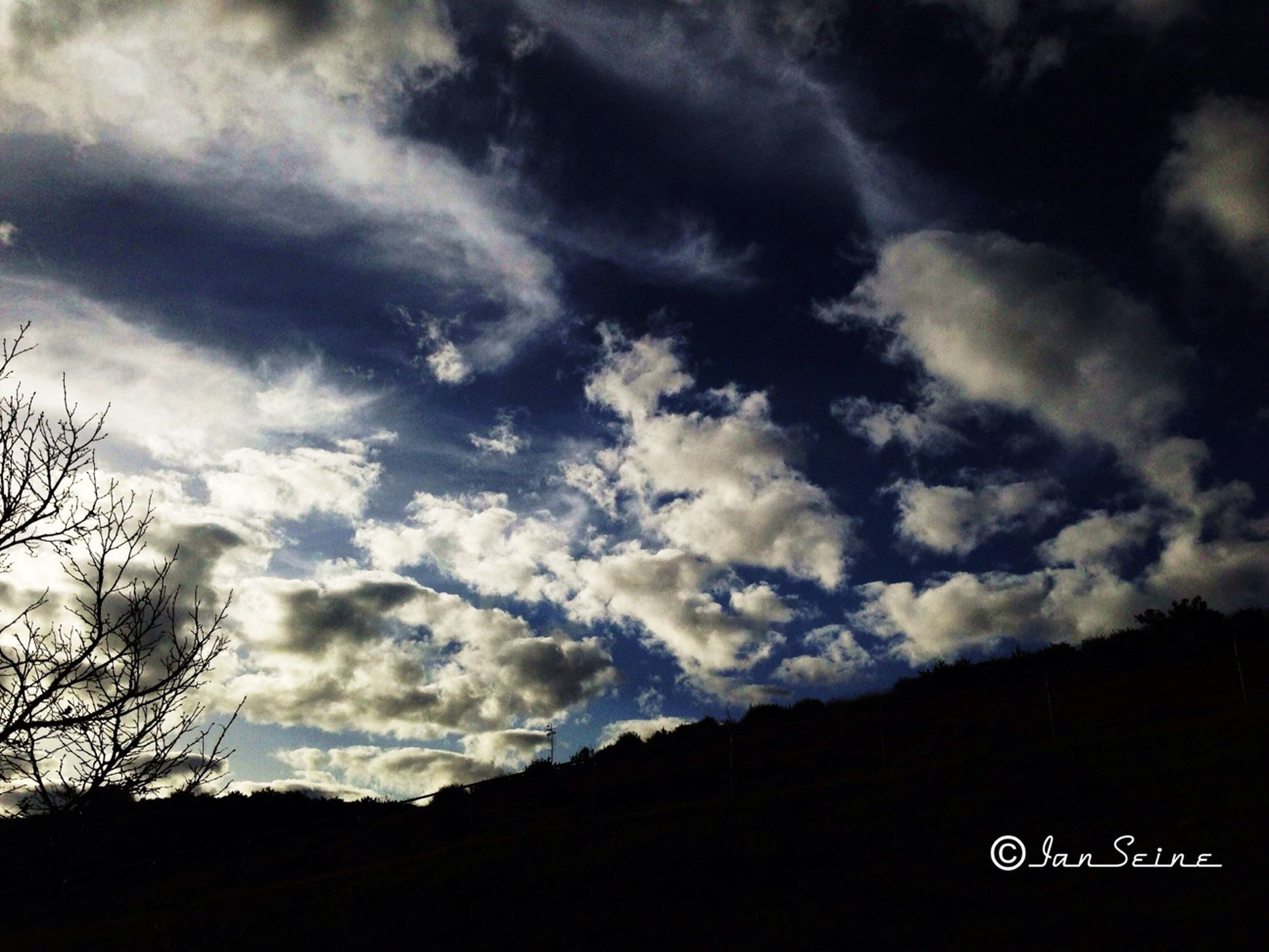 sky, cloud - sky, silhouette, cloudy, tranquility, tree, tranquil scene, scenics, cloud, beauty in nature, nature, landscape, text, low angle view, communication, western script, outdoors, no people, overcast, mountain