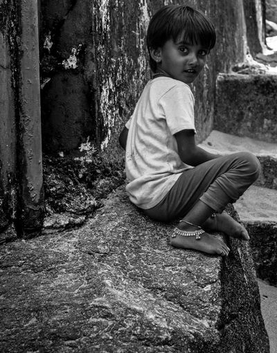 Side view portrait of girl sitting on wall